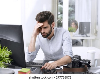 Portrait of worried young businessman sitting in front of computer at office.