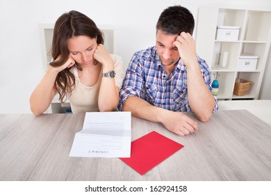 Portrait Of A Worried Young Couple Looking At Paper