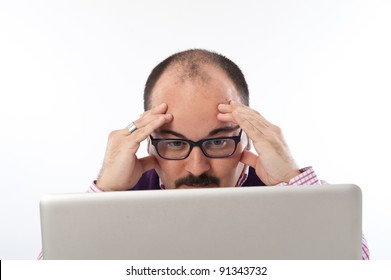 Portrait of a worried young man looking at laptop against white background.