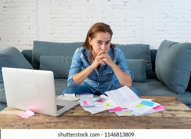 Portrait of worried young single mother feeling stressed while working through finances with laptop and calculator in living room in paying off debts and domestic bills and financial problems concept.