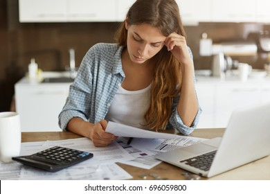 Portrait of worried young single mother feeling stressed while working through finances in kitchen late at night, thinking how to pay off debts for rent and domestic bills. Financial problems concept
