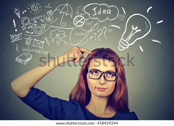 Portrait worried young woman thinking dreaming has many ideas looking up at plan isolated grey wall background. Decision making process concept.
