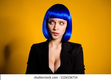 Portrait of worry confused woman in bright blue wig black jacket having sexy decollete big boobs biting low lip looking to the side isolated on yellow background