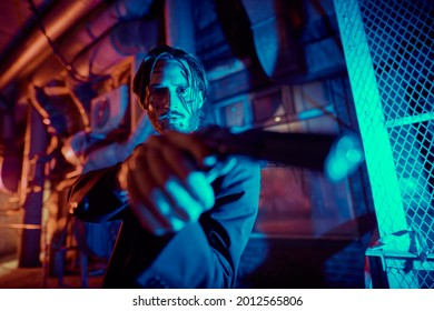 Portrait of a wounded action hero man aiming a gun in the light of the night city.