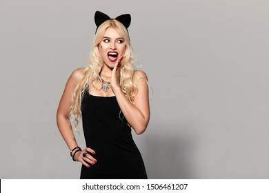 portrait of wow sexy young woman in black witch halloween costume with cat ears in black dress on party over gray background. the concept of Halloween . funny face