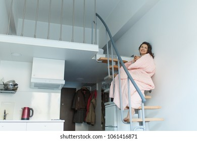 a portrait wrapped in a pink blanket of a girl who early in the morning drinks coffee on the stairs in the apartment