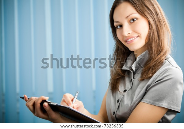 Portrait of writing happy smiling businesswoman working at office. You can use left part for slogan, big text or banner.