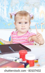 Portrait of a y happy little baby girl at the desk