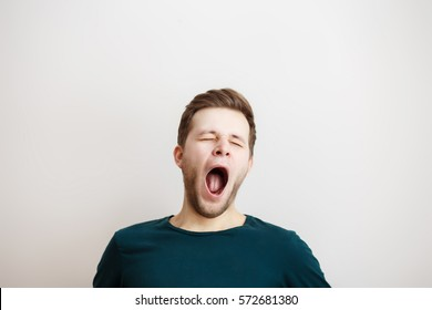 Portrait of yawning man  on a light background