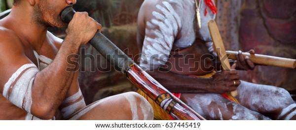 Portrait of Yirrganydji Aboriginal men play Aboriginal music on didgeridoo and wooden  in Queensland, Australia.