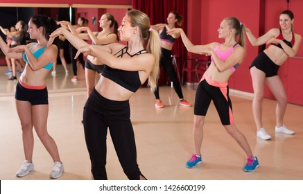 Portrait of young active females training zumba in dance class