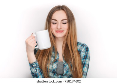 Portrait of a young adorable blonde woman in blue plaid shirt enjoying her warm cozy drink in big blank white mug.