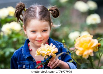 portrait of a young and adorable little girl in  a natural outdoor setting with out of focus roses