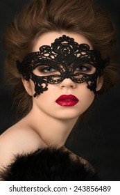 Portrait of young adorable woman wearing black party mask