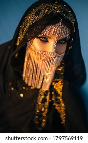 portrait of young adult beautiful sexy oriental mysterious girl. woman looks into camera. face is hidden by golden shiny veil mask. Luxury evening make-up, smoky eyes. head is covered black scarf hood