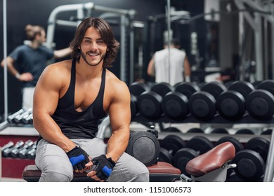 Portrait of young adult Bodybuilder sitting on a bench in a gym and giving the camera a happy friendly smile; concept of health and fitness