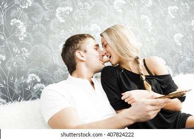 Portrait of young adult caucasian couple sit on white wool couch together eating cookie Man holding sweet between lips Woman bite food Empty texture Copy space for inscription White and black clothes