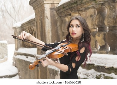 Portrait of young adult cut sexy Girl in black dress with violin on snow and snowy winter fence background Beautiful slim woman with brunette long hair playing music instrument looking up at far away
