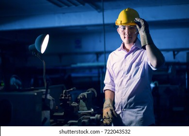 Portrait of young adult experienced industrial asian worker over industry machinery production line manufacturing workshop