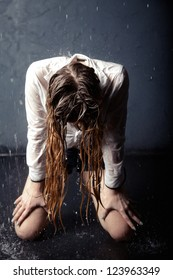 Portrait of young adult girl kneeling by water droplets