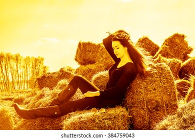 portrait of young adult girl sit on hay block, cute woman rest in field against yellow spring sunset sky with clouds. Female wear black stylish dress and leather high boots. Sunny day on fly long hair