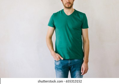 Portrait of young adult handsome man wearing green casualt-shirt and posing near wall. Handsome man posing in studio.