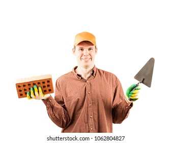 portrait of young adult happy mason tradesman in a red plaid shirt holding red brick with holes and black trowel on gray background Handsome man look at camera with smile wear green rubber gloves