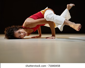 portrait of young adult latin american female doing yoga and capoeira in gym. Horizontal shape, full length, side view, copy space