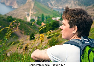 portrait of a young adult male tourist who rest sitting on mountains