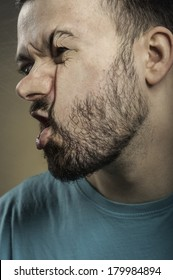 Portrait of a young adult man with beard smashing his face against the scratched glass