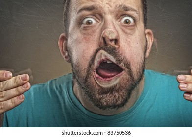 Portrait of a young adult man with beard blowing against the scratched glass making funny face