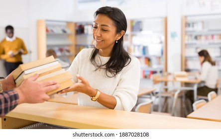Portrait of young adult woman returning books to librarian at public library
