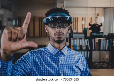 Portrait of young African American black male professional using augmented reality holographic hololens in modern office