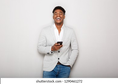 Portrait of young african american businessman laughing with cellphone by gray wall