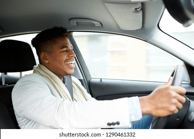 Portrait of young african american businessman driving car