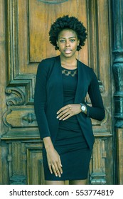 Portrait of Young African American Businesswoman with short afro hairstyle in New York, wearing black fashionable work clothes, wristwatch, standing by vintage office doorway. Color filtered effect