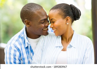 portrait of young african american couple looking at each other outdoors