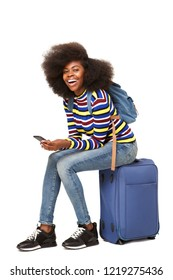 Portrait of young african american female traveler sitting on suitcase with mobile phone