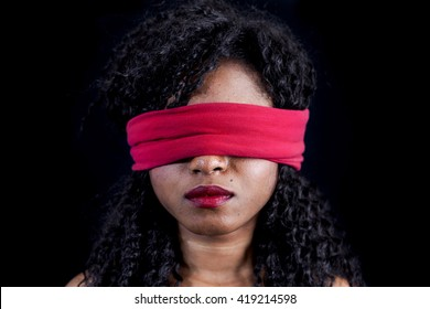 portrait of young african american female with a red blindfold on