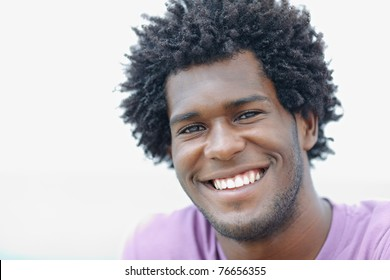 portrait of young african american guy looking at camera near the sea. Horizontal shape, head and shoulders, copy space