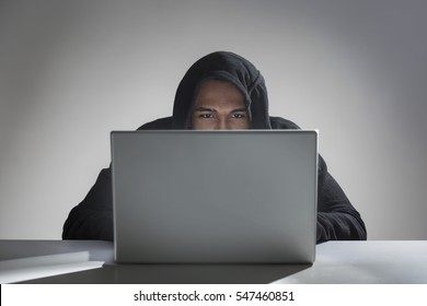 Portrait of a young African American hacker sitting at his gray laptop in a hoodie and coding. Concept of stealing and internet crimes. Mock up