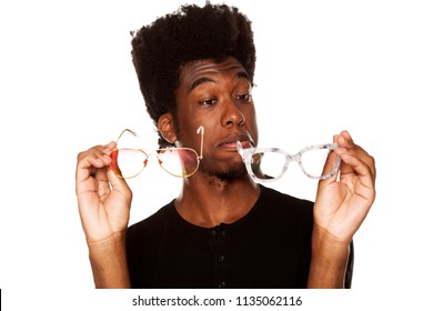 Portrait of young african american man chooses between two pairs of glasses on white background