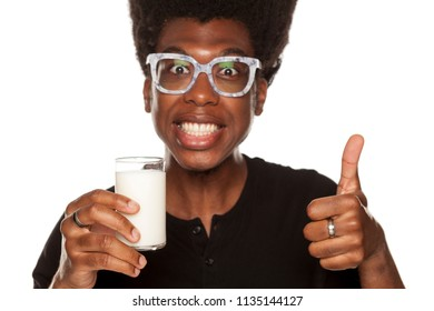 Portrait of young african american man drinking yogurt from a glass on white background