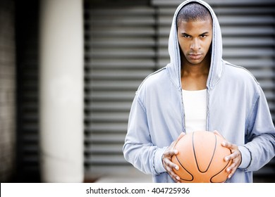 Portrait of a young African American man in a grey hooded top holding a basketball.