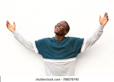 Portrait of young african american man looking up with his arms wide open on white background