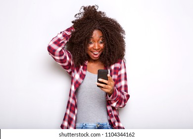 Portrait of young african american woman looking at mobile phone with surprised expression on white background