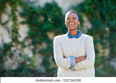 Portrait of a young African American woman laughing while standing with her arms crossed outside in her yard on a sunny day