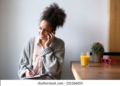 Portrait of a young african american woman talking on mobile phone and taking notes