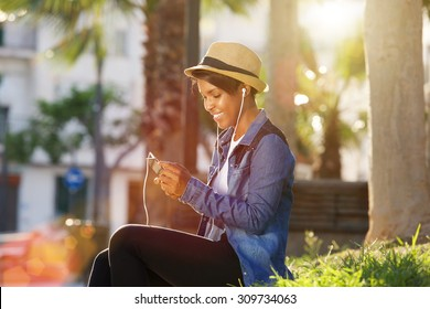 Portrait of a young african american woman listening to music on cell phone