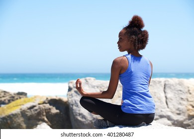 Portrait of young african american woman sitting a rock at beach in yoga pose